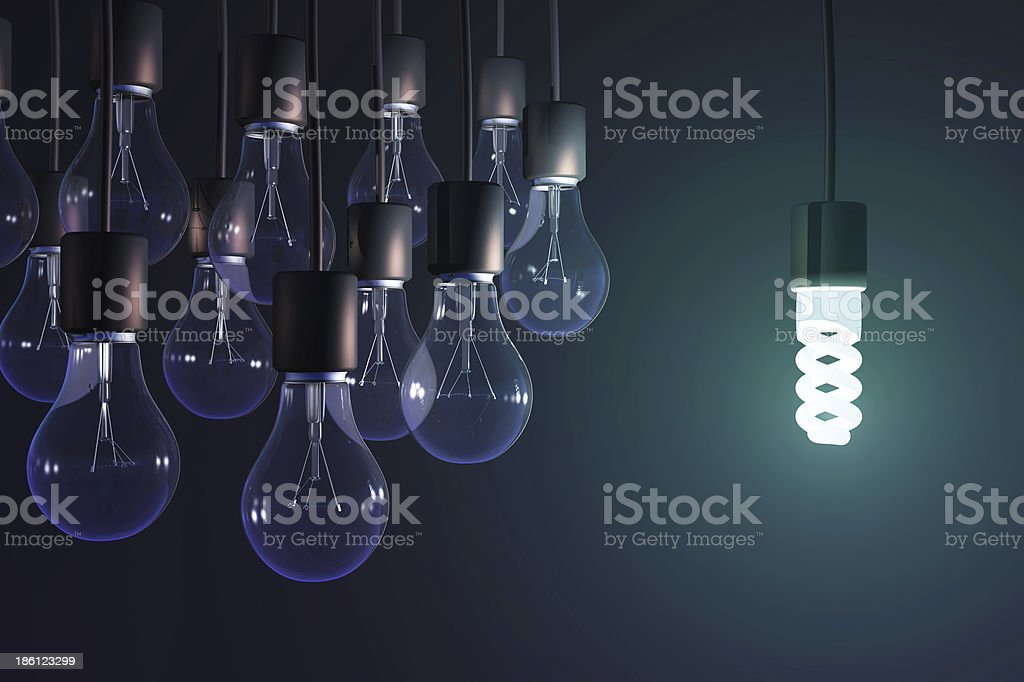 energy-saving lamp among the gray bulb royalty-free stock photo