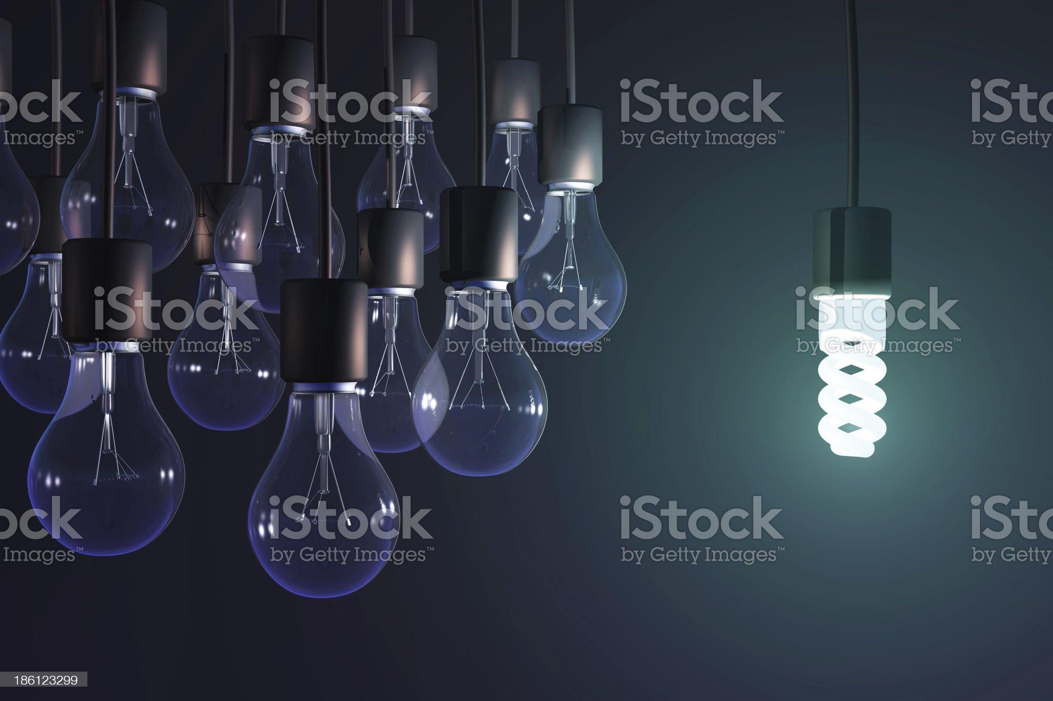 energy-saving lamp among the gray bulb royalty-free stock photo