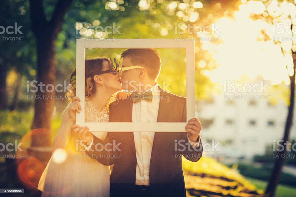 Engaged couple frames their kissing at sunset stock photo