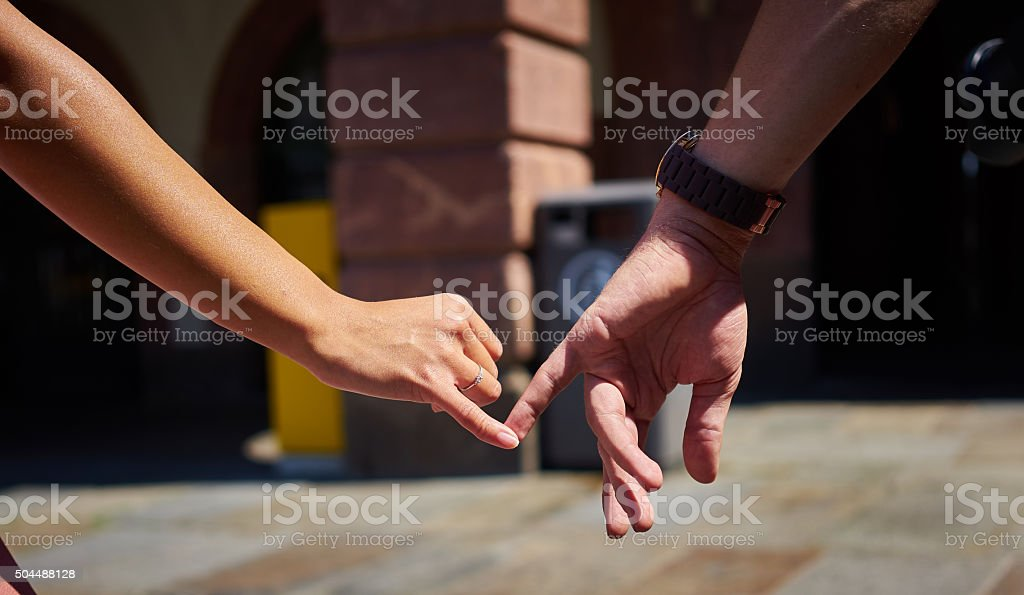 Engaged couple walking in city and holding hands stock photo