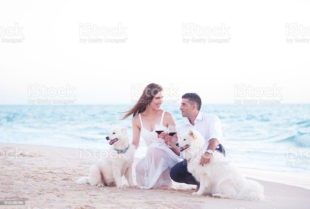 Engaged couple with white dogs celebrating at seashore. stock photo