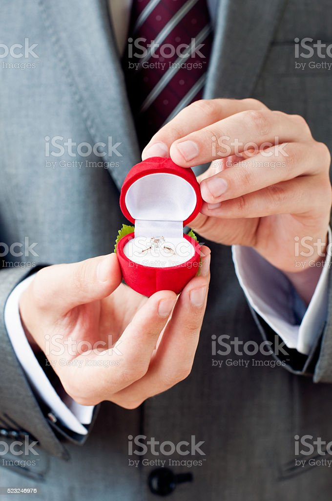 Engagement ring in male hands stock photo