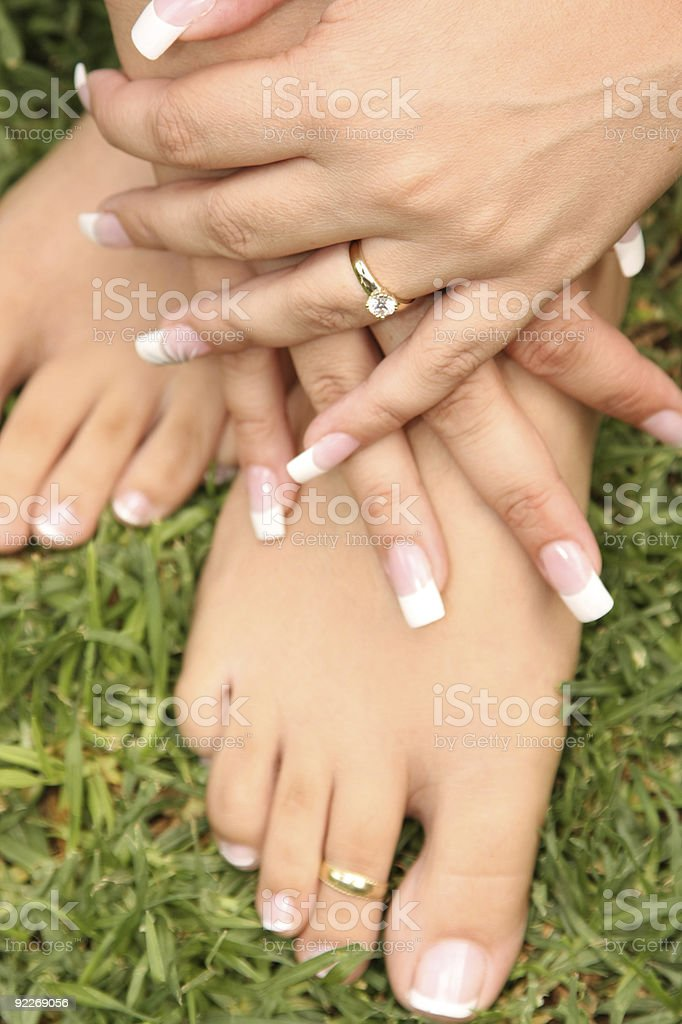 Engagement ring on hands holding feet stock photo