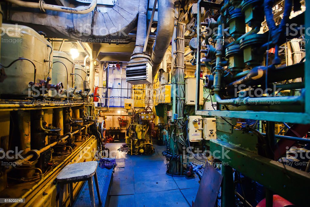 Engine room on a cargo boat ship with gears stock photo