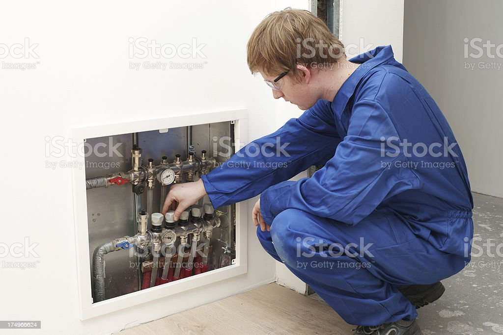 Engineer adjusting under floor heating valves royalty-free stock photo