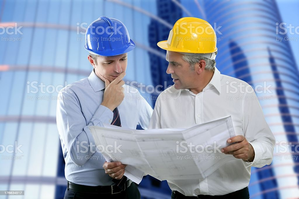 Engineer and architect wearing hard hats and planning royalty-free stock photo