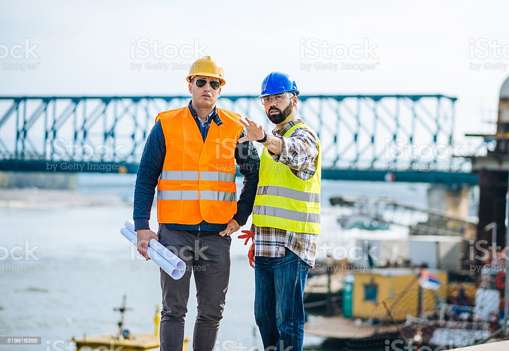 Engineer and construction site manager dealing with blueprints and projects stock photo