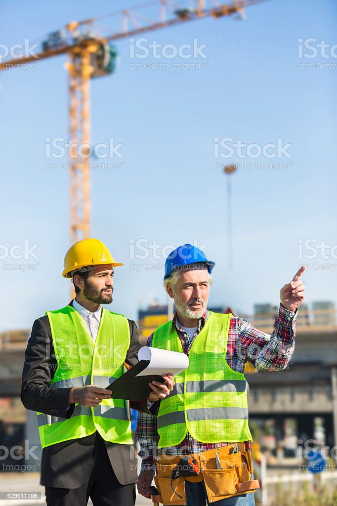 Engineer and construction site manager dealing with blueprints and plans royalty-free stock photo