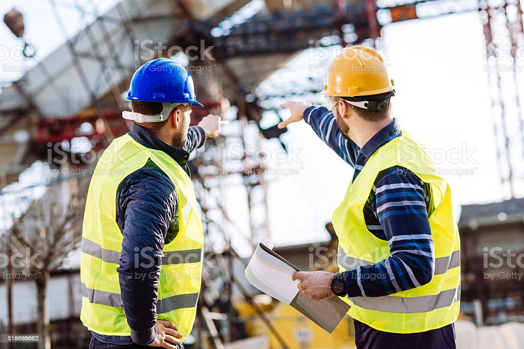 Engineer and construction site manager dealing with next construction phase stock photo