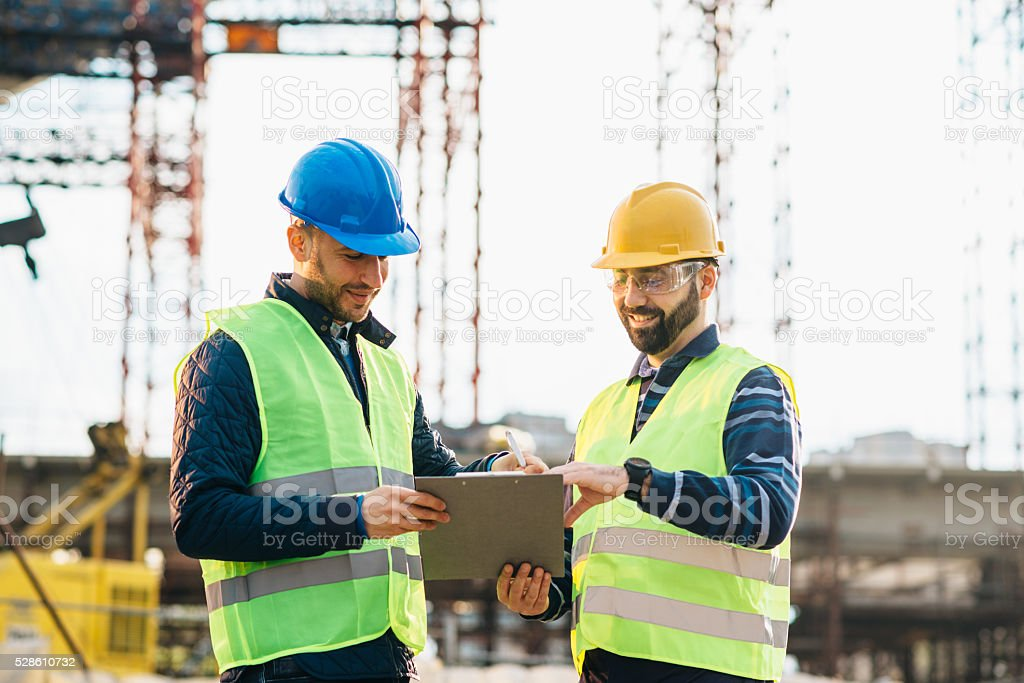Engineer and construction site manager discussing next construction phase stock photo
