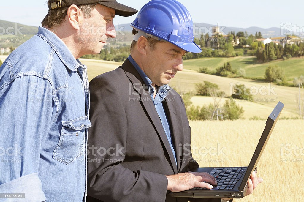 Engineer and Farmer Planning in the Countryside royalty-free stock photo