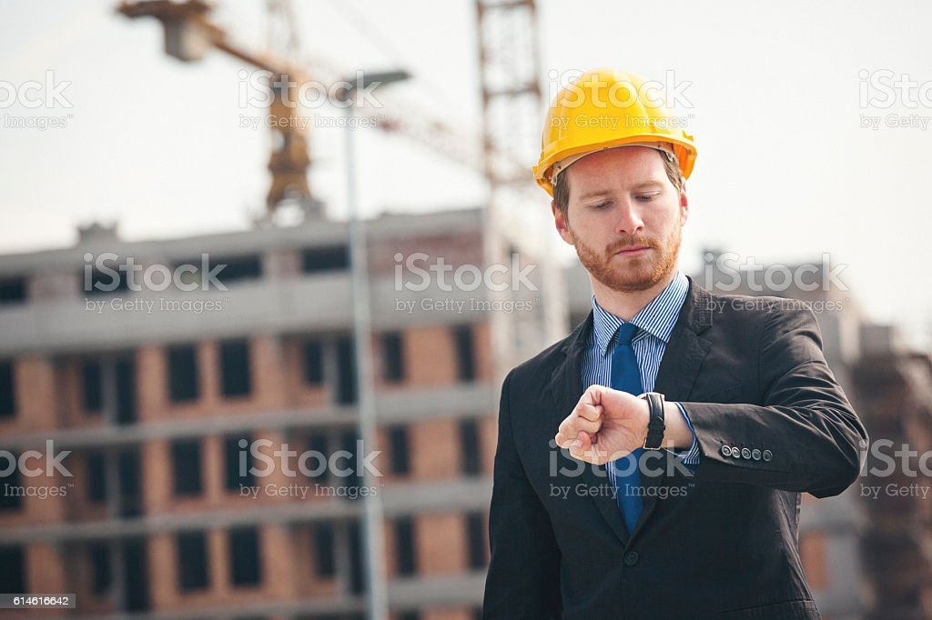 Engineer at construction site checking the watch stock photo