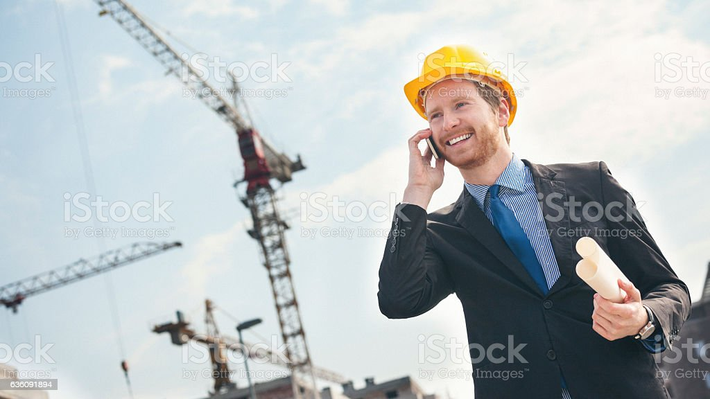 Engineer at construction site talking on the phone stock photo