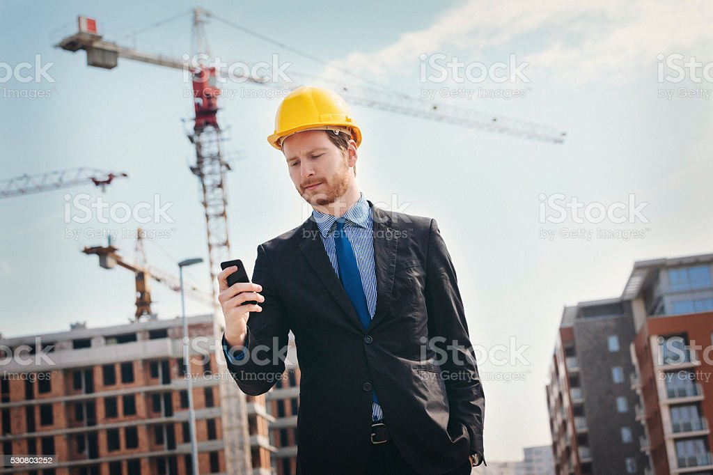 Engineer at construction site using smart phone stock photo