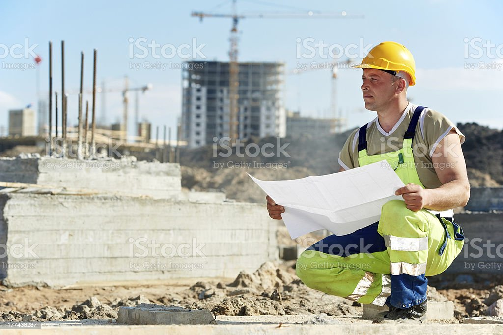 Engineer builders at construction site with draft royalty-free stock photo