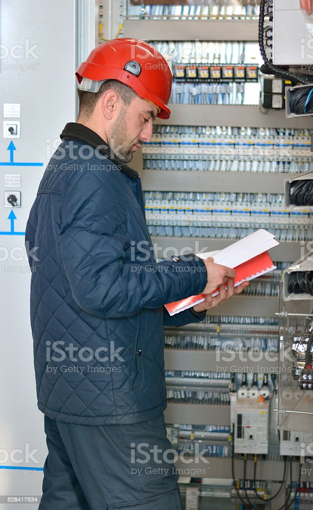 Engineer Checks if the Cables are well Connected to Fuses stock photo