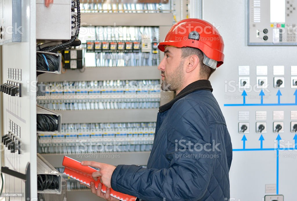 Engineer Checks the Functionality of the Equipment in Electrical Room stock photo