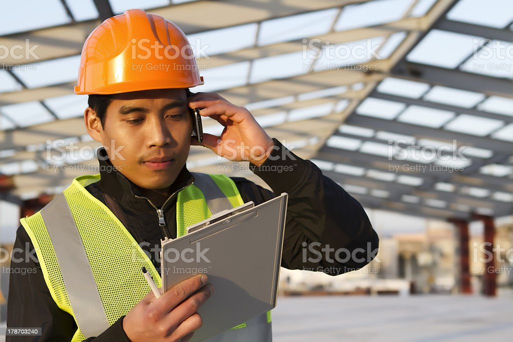 Engineer construction talking mobile phone under new building stock photo