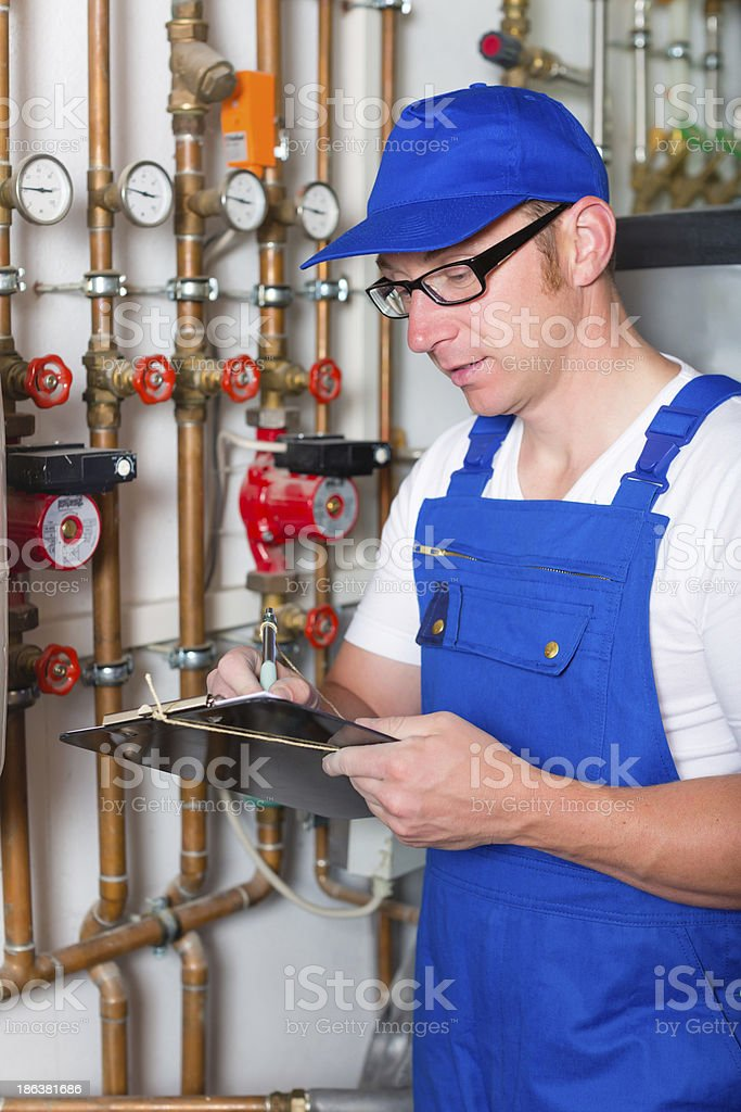 Engineer controlling the heating system royalty-free stock photo