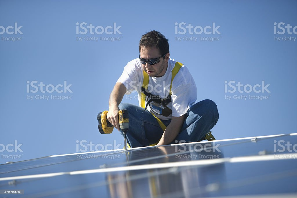 Engineer Drilling Solar Panel Against Blue Sky royalty-free stock photo