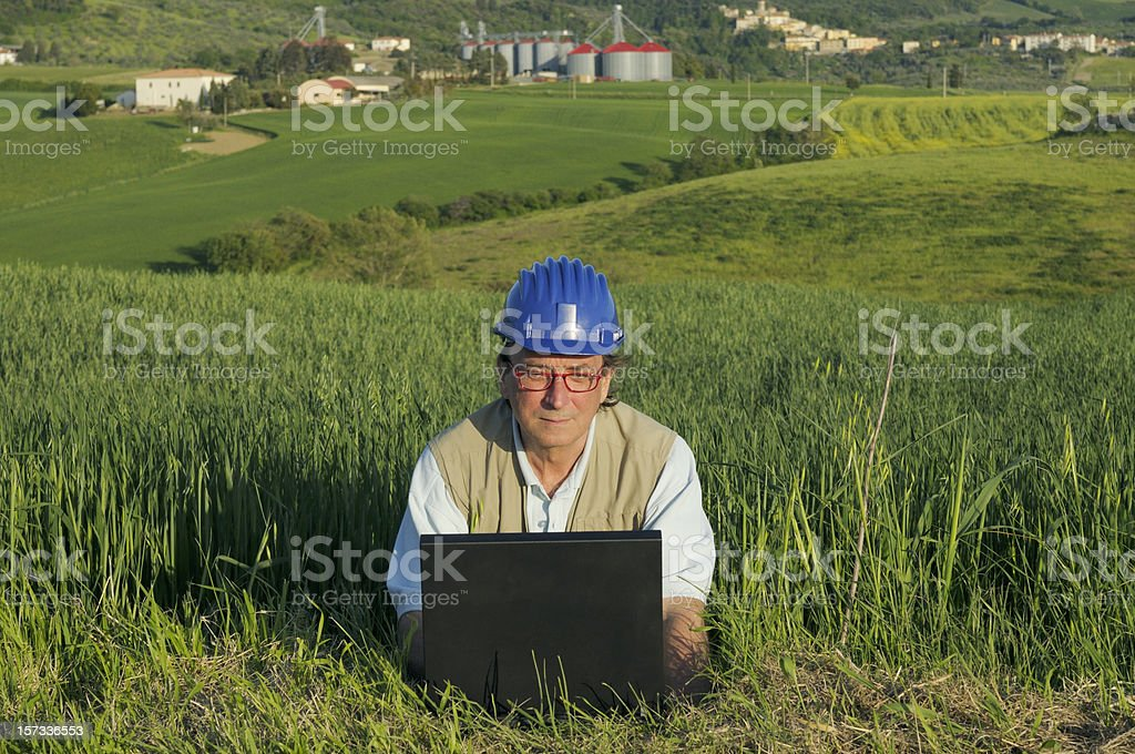 Engineer Examining Project PC in a Green Field royalty-free stock photo