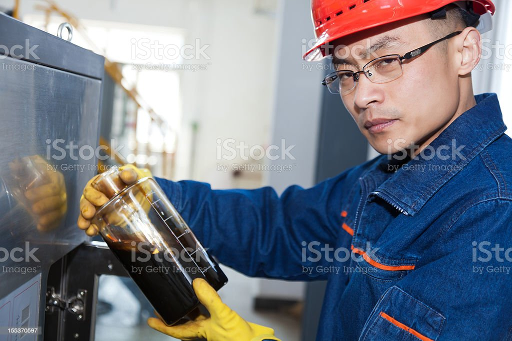 Engineer examining the sample of oil royalty-free stock photo