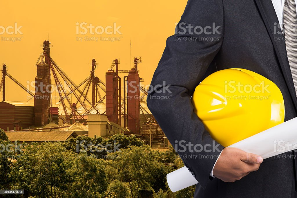 engineer hand holding yellow helmet for workers security and blu stock photo