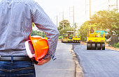 engineer holding helmet at road construction site