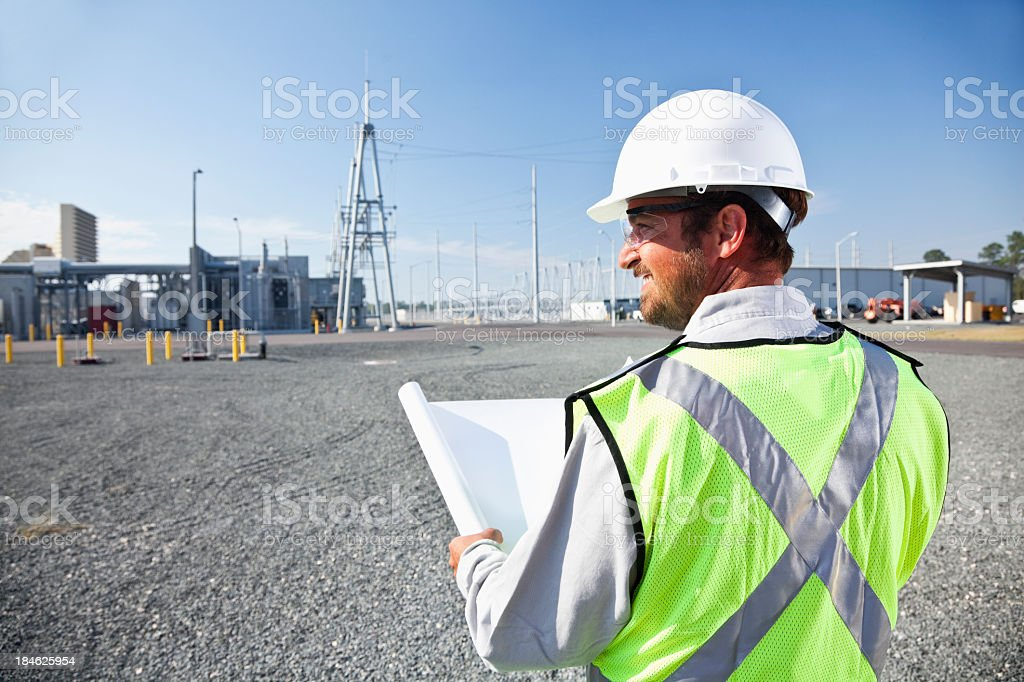 Engineer holding plans surveying power station royalty-free stock photo