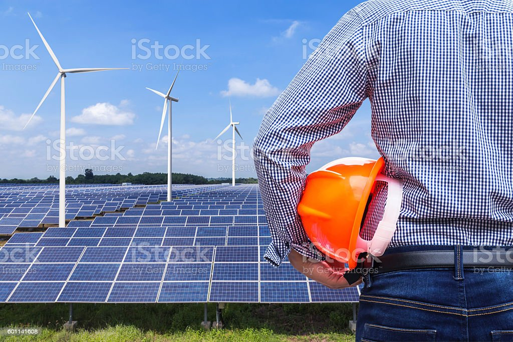 engineer holding safety helmet front photovoltaic and wind turbines station stock photo