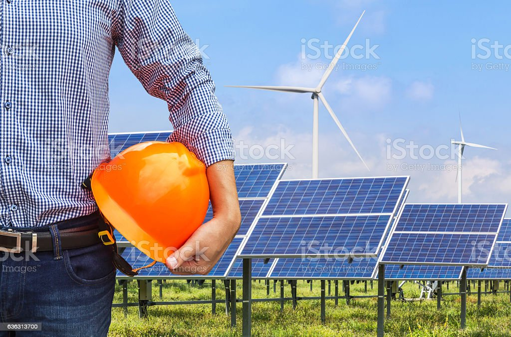 engineer holding safety helmet front photovoltaics and wind turbines station stock photo