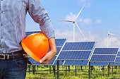 engineer holding safety helmet front photovoltaics and wind turbines station