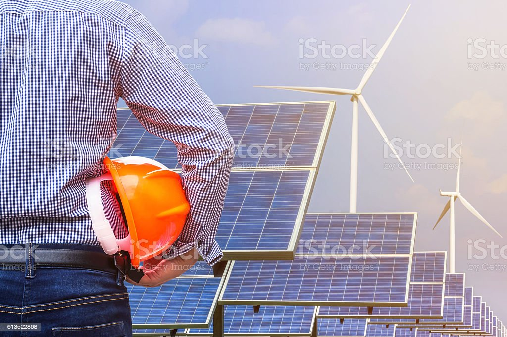 engineer holding yellow helmet front photovoltaic and wind turbines electricity stock photo