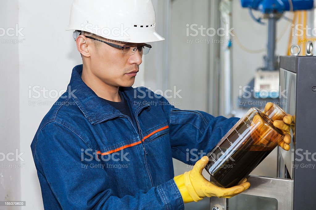 Engineer in hard hat examining an oil sample  stock photo