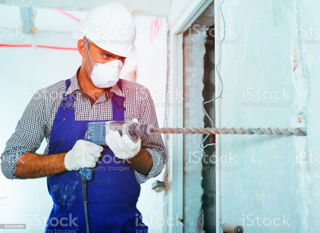 Engineer in helmet is perforating wall with drill stock photo