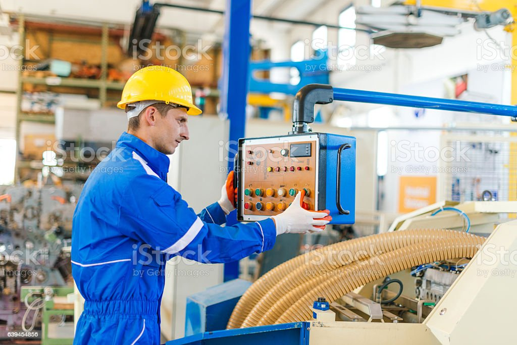Engineer in protective suit and hardhat working in factory stock photo