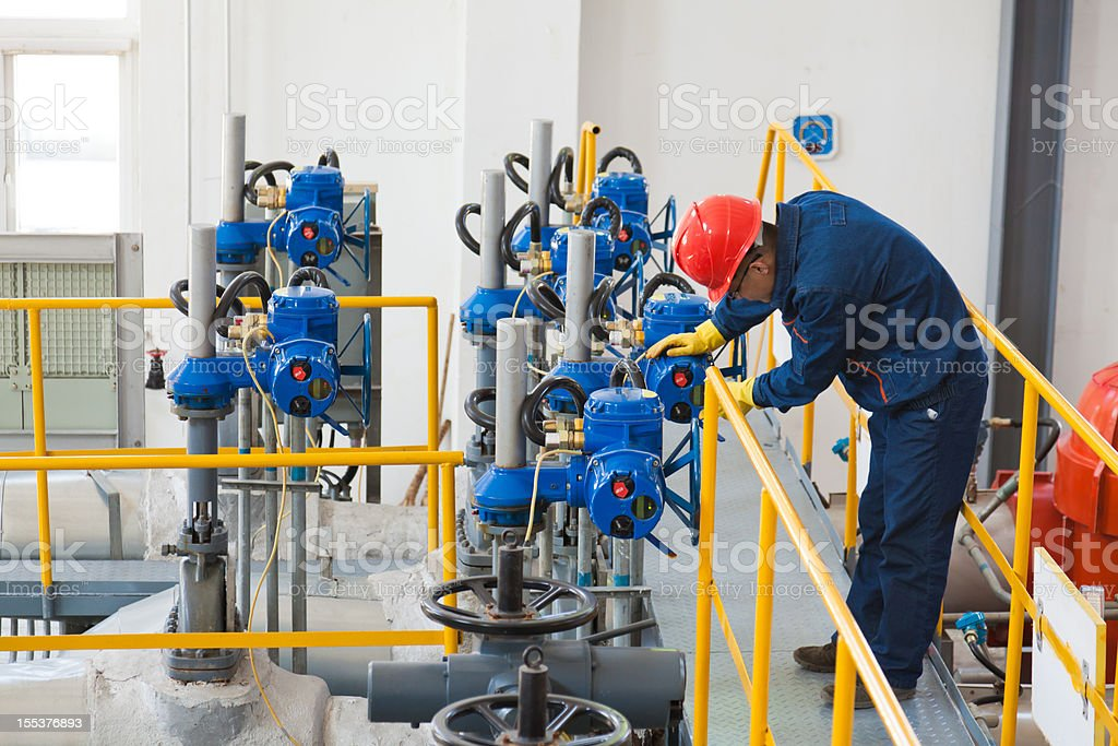 Engineer in protective wear checking oil pipes equipment royalty-free stock photo