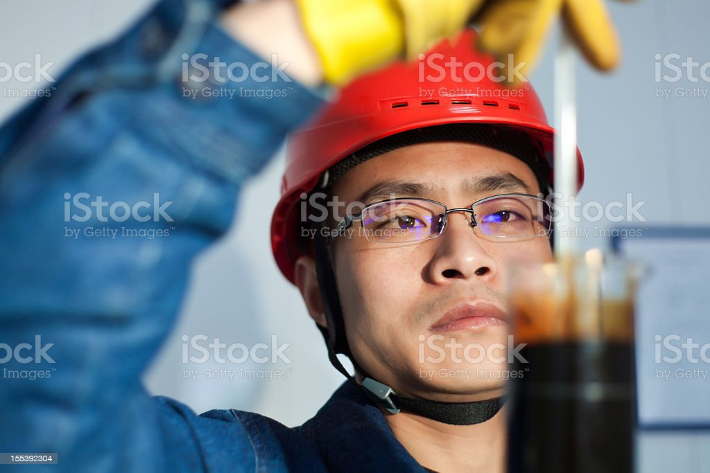 Engineer in red helmet with yellow gloves taking a sample stock photo