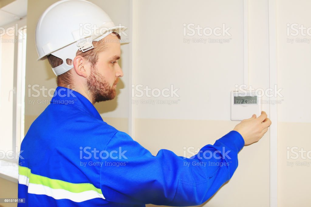engineer in the white helmet sets the temperature on the control panel of the air conditioner stock photo