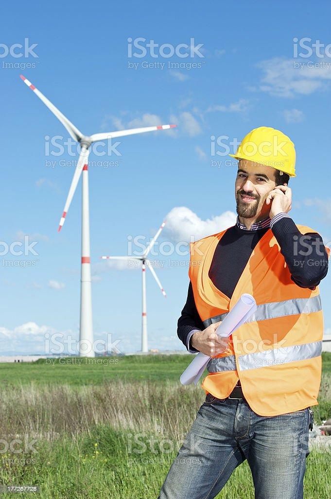 Engineer in Wind Turbine Power Generator Station, talk at phone royalty-free stock photo