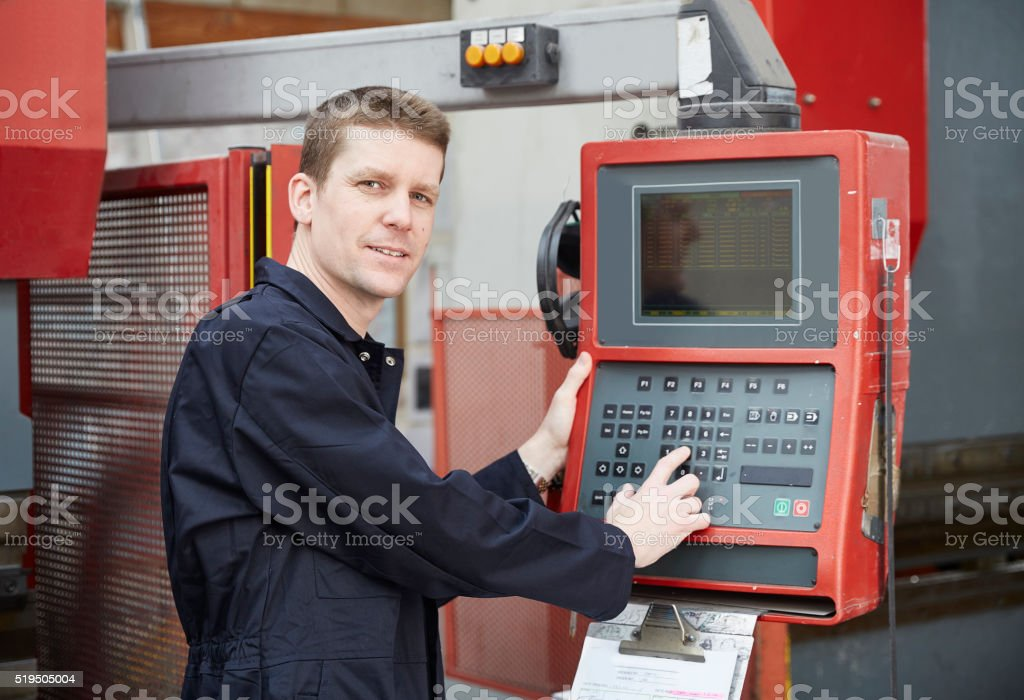 Engineer inputting data into CNC metal press stock photo