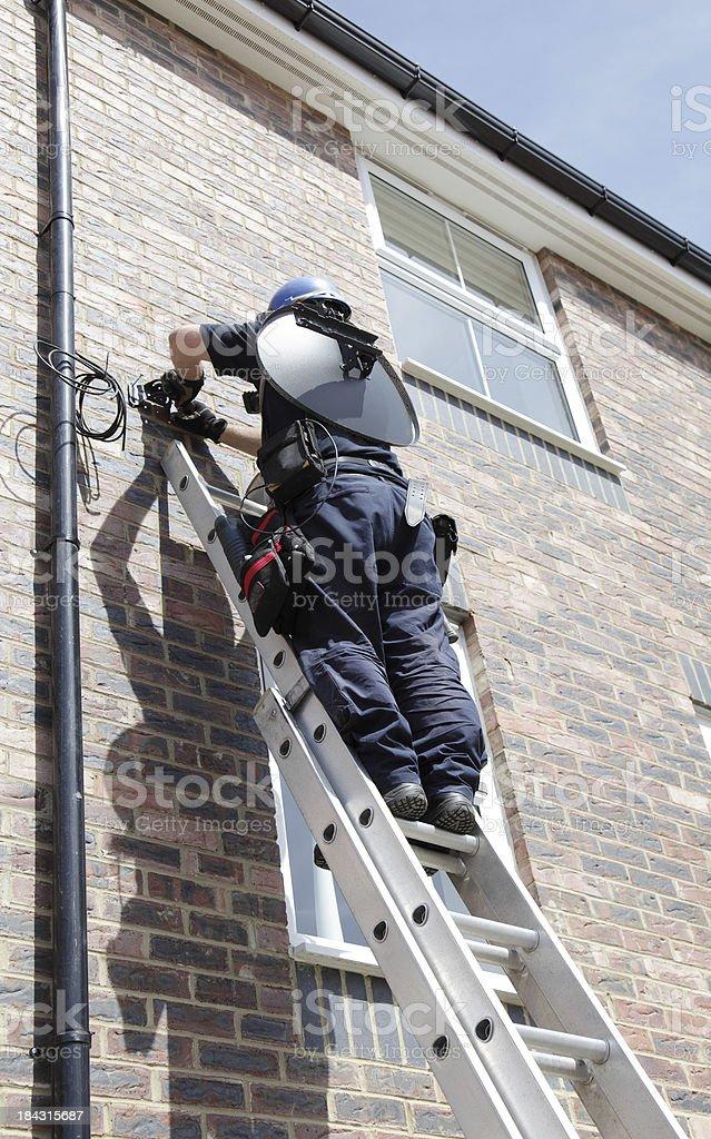 engineer installing a satellite dish stock photo