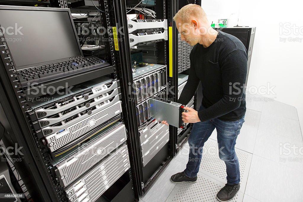 IT engineer installs blade server in datacenter stock photo