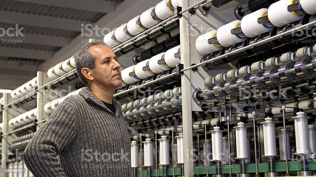 Engineer is Looking at the Machines in Textile Factory stock photo