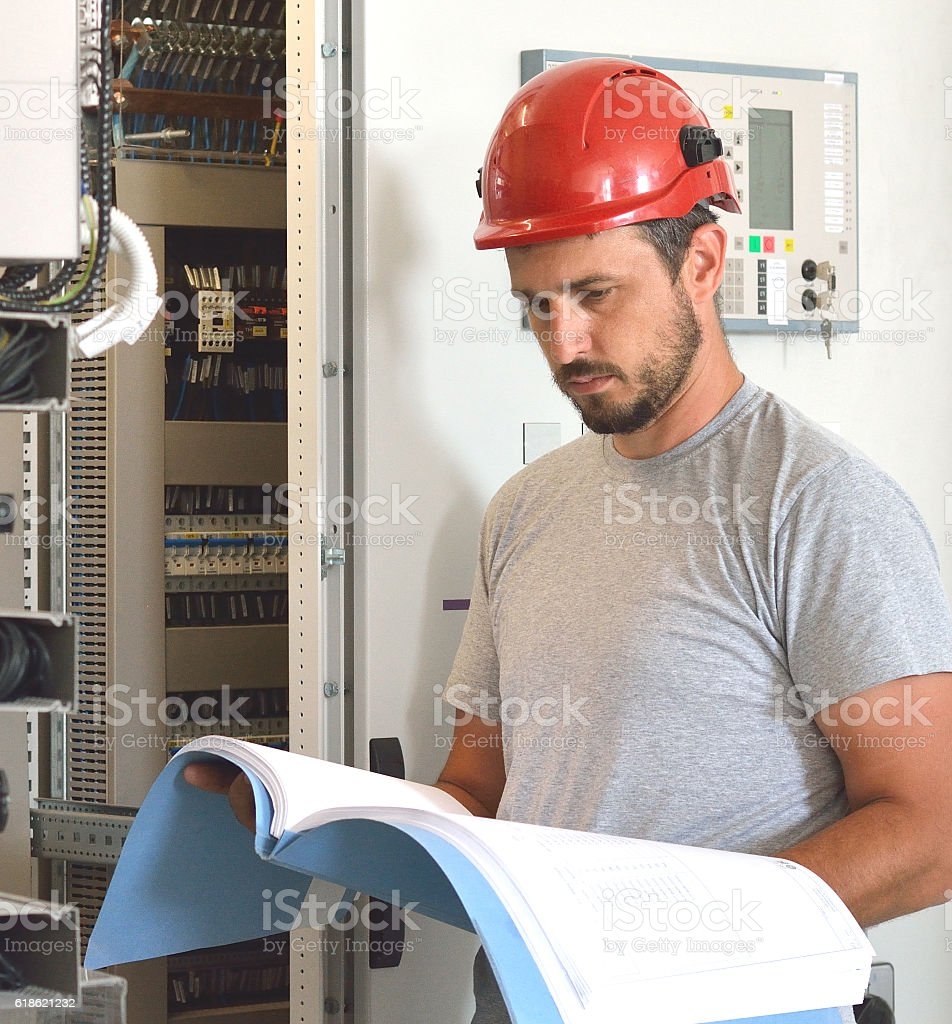 Engineer Looking at Blueprints and Checking Equipment in Control Room stock photo