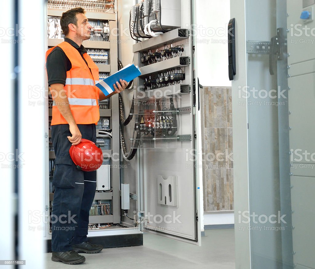 Engineer Looking at Blueprints and Checking Equipment in Electrical Room stock photo