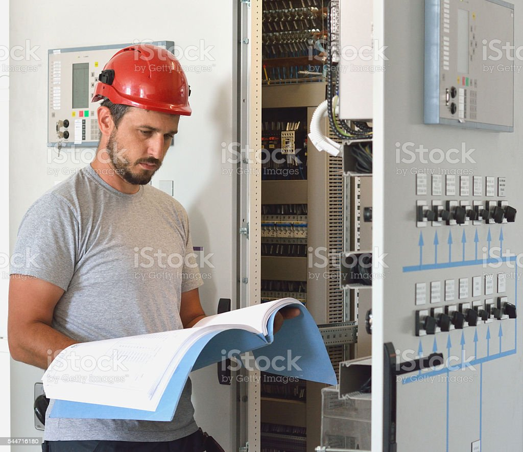 Engineer Looking at Blueprints in Control Room stock photo