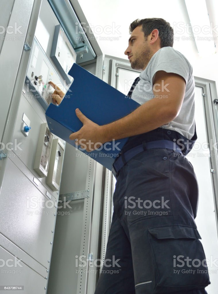 Engineer looking at file in control room stock photo