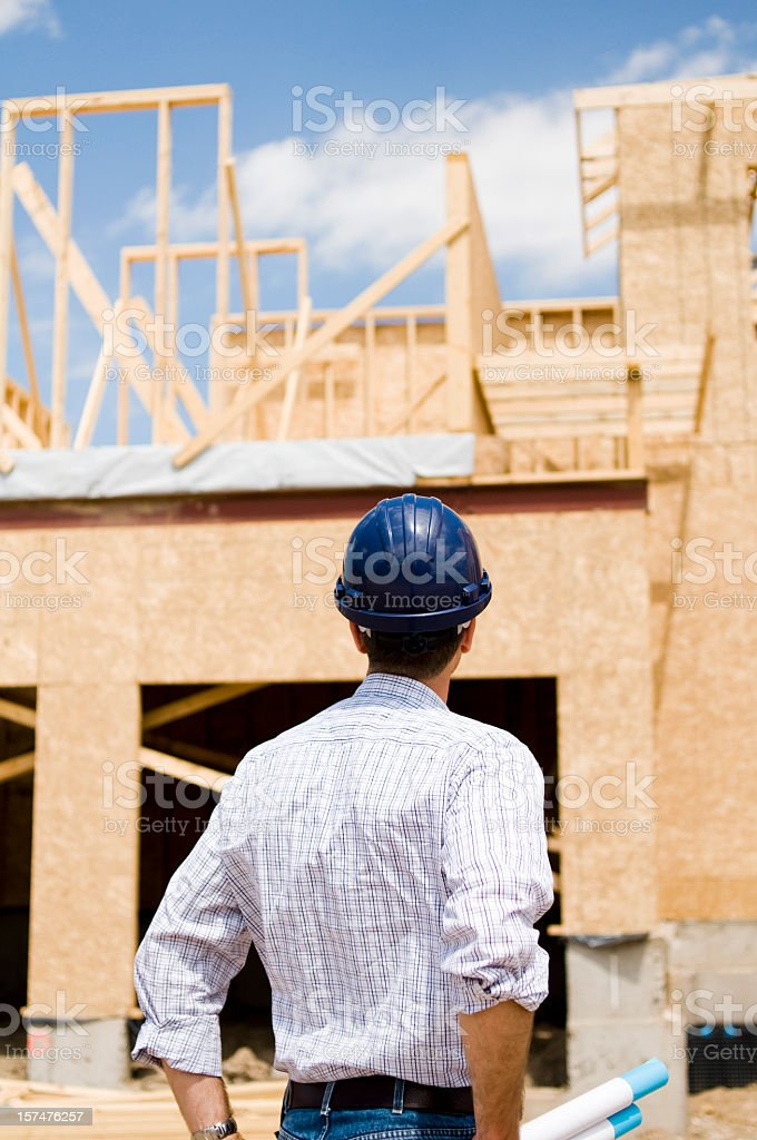 Engineer looking up at a building under construction stock photo
