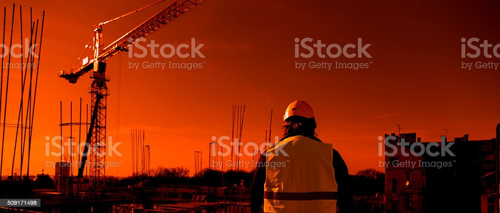 engineer looks at a construction site at sunset stock photo